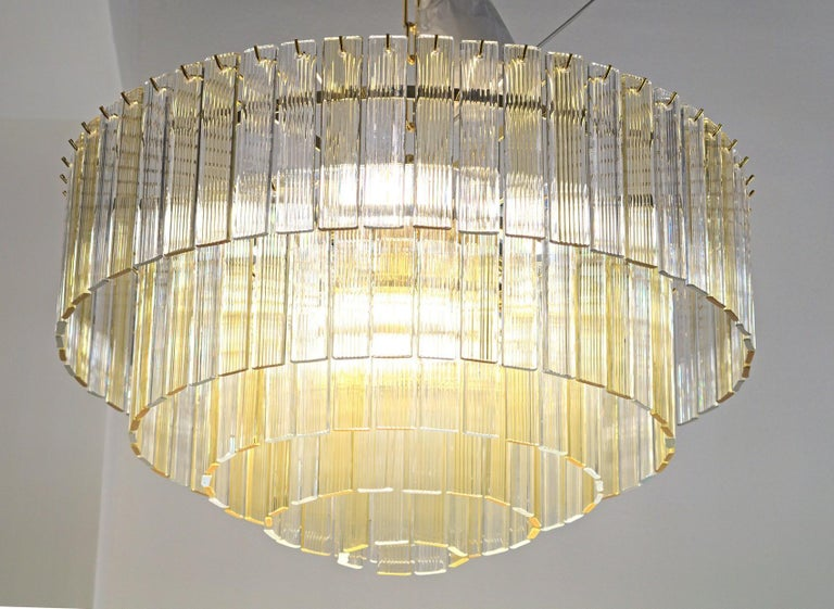 Cascading chandelier made using the Fettucce elements. These are not blown or poured. The glass is shaped and then stretched like the triedri. Classic Venini combination with amber and clear. This was made to give warm golden light without changing