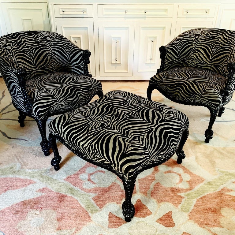 A rare pair of Napoleon lll carved rope and tassel chairs and matching ottoman by Weiman  The frames are in black lacquer with zebra upholstery - all hand carved and in great condition. The ottoman is curved to easily place next to the chair