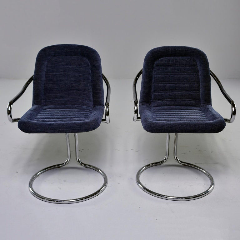 Found in Italy, this pair of circa 1970s armchairs feature polished chrome frames with a circle form base and curved arms. Seats are scoop shaped with new navy blue chenille upholstery. The base gives these chairs a bit of bounce and give. Unknown