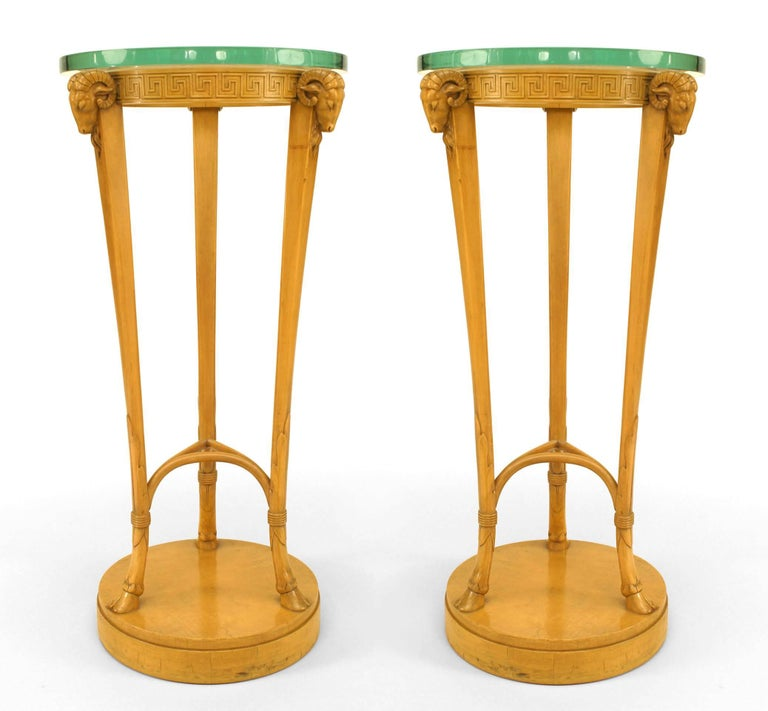 The sycamore pedestals with original round glass tops above an apron of three ram heads and Greek key design supported by three tapering legs running into hoof feet all on a round plinth