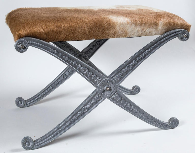 Pair of Neoclassic X-frame upholstered benches, 20th century. Metal frames with matte silver finish and impressed floral design. Slip seat cushions upholstered in pony hair.