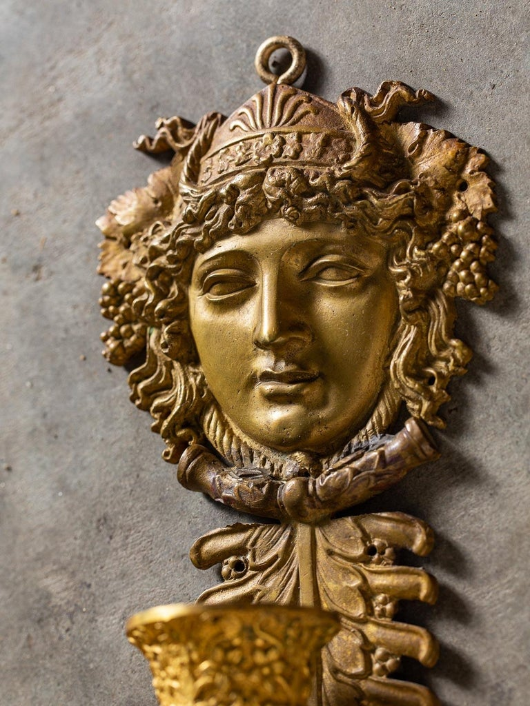 A pair of neoclassical antique French gilt bronze sconces Napoleon III period circa 1870. This pair of three arm French sconces feature a bold portrait head of Bacchus Dionysus (look at the entwined grape clusters and grape leaves entwined in the