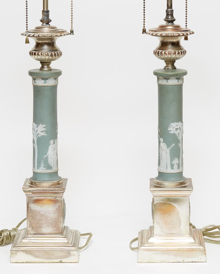 Pair of table lamps in the neoclassical style, with standards of Jasperware porcelain in Roman column form, with square silver gilded bases with classical Jasperware medallions. Possibly from Wedgwood.