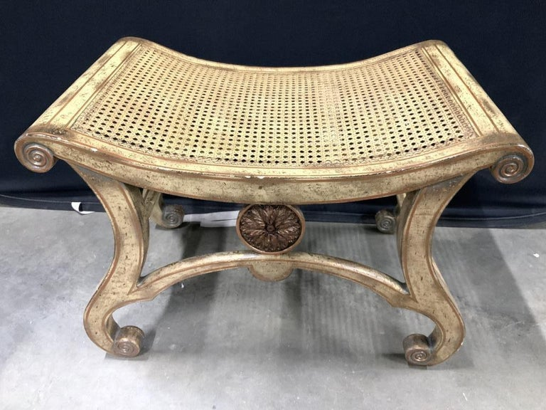 A pair of neoclassical stools in the Empire style, the stools have caned seats, wood is carved and gilded in the classical style. The stools or benches with caned seats in light yellow tone with areas which appear to be gold leafed. Upper and lower