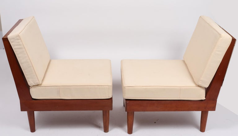 Pair of architectural New Hope style Mid-Century Modern American studio furniture lounge chairs with loose cream-color loose cushions.  Angled, ladder-backs and dowel-form legs, signed