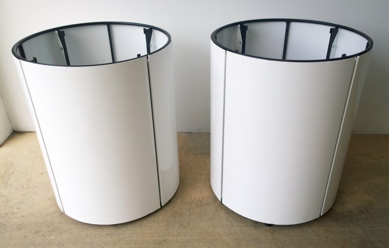 Offered is a Mid-Century Modern pair of newly powder-coated in white over metal panels attached to a black metal frame large planters. The planters each have a concrete square block at the base for stabilization. The planters drain through the