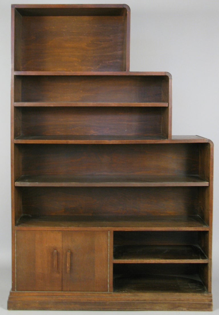 a very handsome pair of 1940s walnut bookcases in a skyscraper form, with adjustable shelves in two of the sections in each bookcase. the pair are designed as mirror images, so that if placed side by side they make a complete skyscraper form.