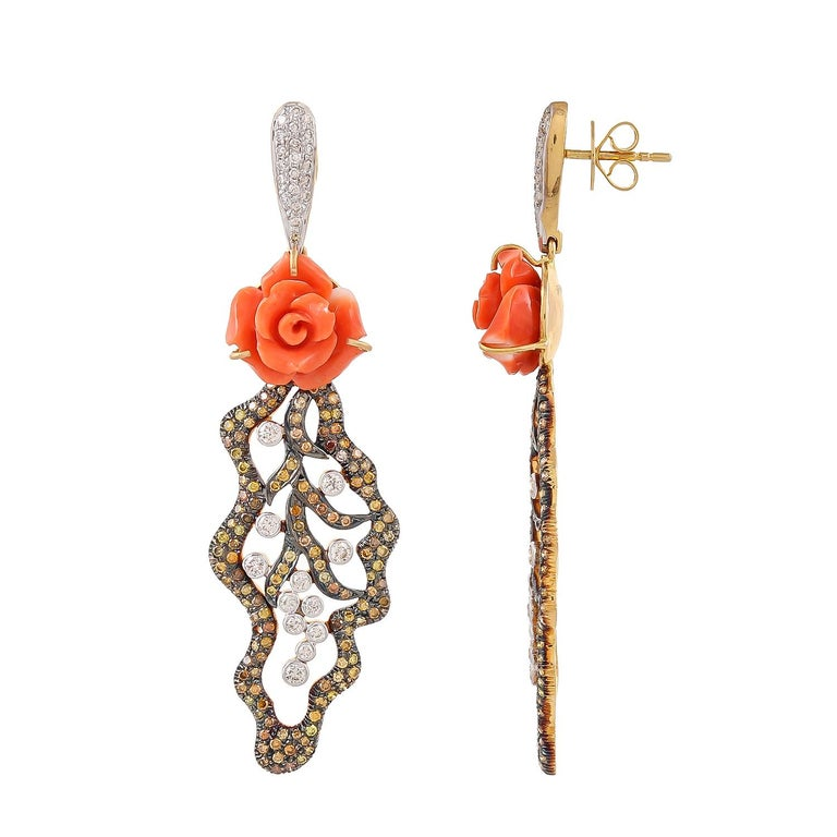 Crafted in 18 karats yellow gold, this one-of-a-kind earring features beautiful and delicate carved coral flower weighing approximately 12.05 carats and dangling foliate motif set with 1.89 carats fancy brown diamonds and 1.05 carats white diamonds.