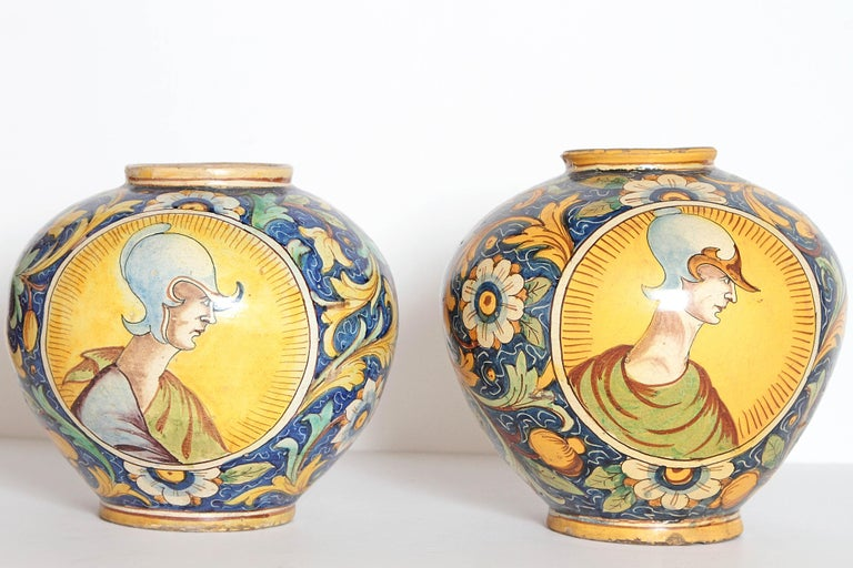 A pair of Northern Italian / Venetian Maioloca drug jars (vases) of globular form (vaso a palla or ball vase) decorated with two portrait medallions on a blue ground, one side a helmeted warrior, the other with that of a young man, scrolling foliage