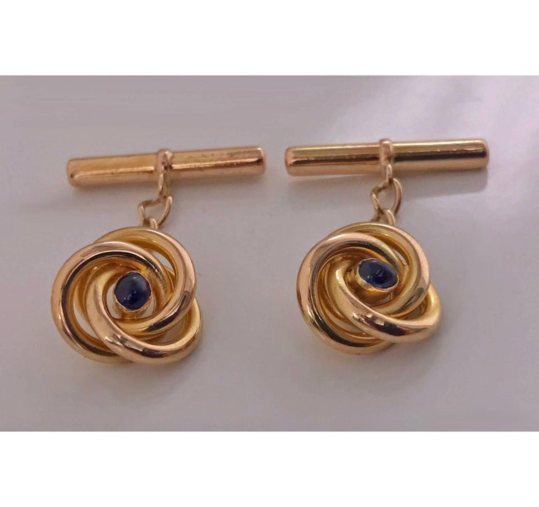 Pair of 18K (tested) Sapphire  Cufflinks, C.1930. Each of open swirl knot design, set with small oval cabochon blue sapphire, 14K t bar fitments chain link between. Total Item Weight: 4.59 gm. Continental mark, possibly French.