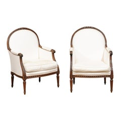Pair of 1830s French Restauration Carved Walnut Upholstered Bergères Chairs