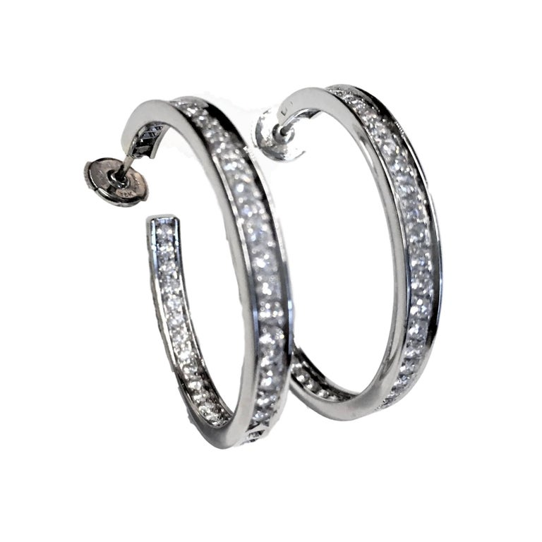 18k white gold Cartier diamond hoop earrings. Each set with round brilliant cut diamonds. Total weight of approximately 3ct,  The earrings measure 34mm in height and 2.5mm in width and  Posts with alpa back fittings.  Signed Cartier. Numbered.