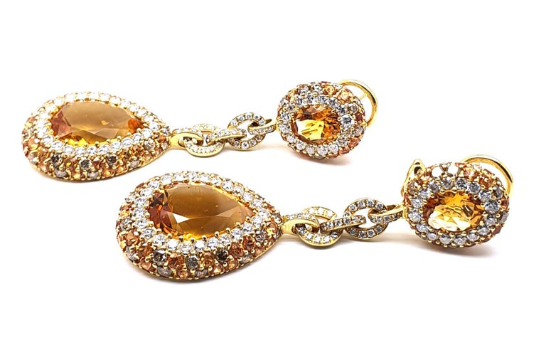 A pair of 18Krt yellow gold earrings (pendant) occupied with 10.96ct Citrine, 3.43ct orange Korund, 2 and 2.22ct brown brilliantly sharpened Diamonds. 18 K Yellow Gold is 13.08 grams