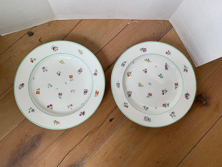Pair of 18th-19th century French sprig pattern porcelain round chargers with green trim, unmarked.