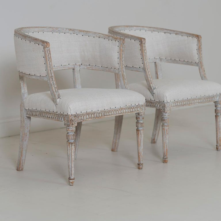 A pair of stylish Swedish chairs with classic sulla barrel backs from the Gustavian period wearing original paint and newly upholstered in linen. Beautifully carved bell flowers around the backs of the chairs with carved egg and dart detail on the