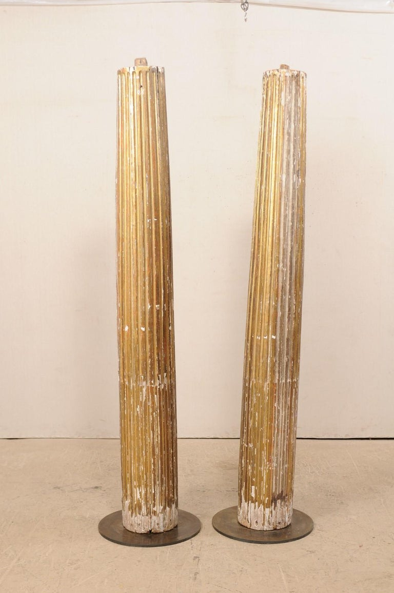 A pair of Italian fluted and giltwood columns from the 18th century. This antique pair of tall architectural columns from Italy feature fluted, and rounded bodies, tapering slightly towards their top, with a fabulous old chippy patina and gilt. Each