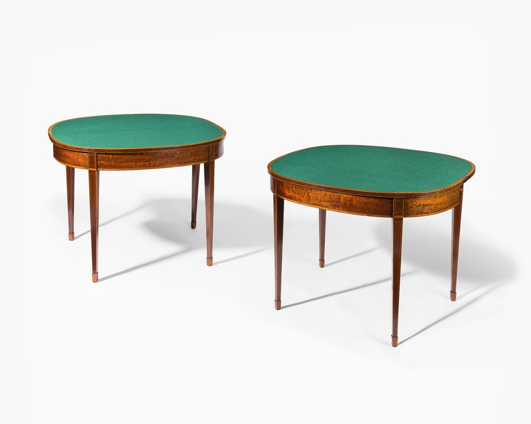 A good pair of 18th century George III period, mahogany veneered D-shaped card tables. Each fold over top opens to a green baize interior. The whole is cross-banded in satinwood with ebony and boxwood stringing throughout.
