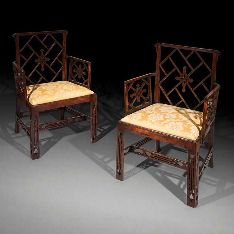 Pair of George III Chinese Chippendale mahogany armchairs, after a design by Mayhew & Ince, circa 1760.  Each with a piercedgeometric back betweenconforming lattice armrests,above drop-in seats, recently covered in yellow silk damask,pierced
