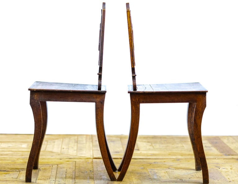 A beautiful pair of Georgian country house oak hall chairs constructed in a plain and simple shape with lovely proportions. The shaped rectangular back frames a central raised lozenge above a square seat raised on sable legs.