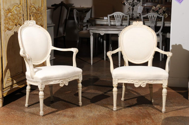A pair of Danish 18th century Louis XVI painted wood oval back armchairs with bow motifs, scrolled arms and new upholstery. Born in Denmark during the 18th century, each of this pair of wooden armchairs features an oval back accented with a