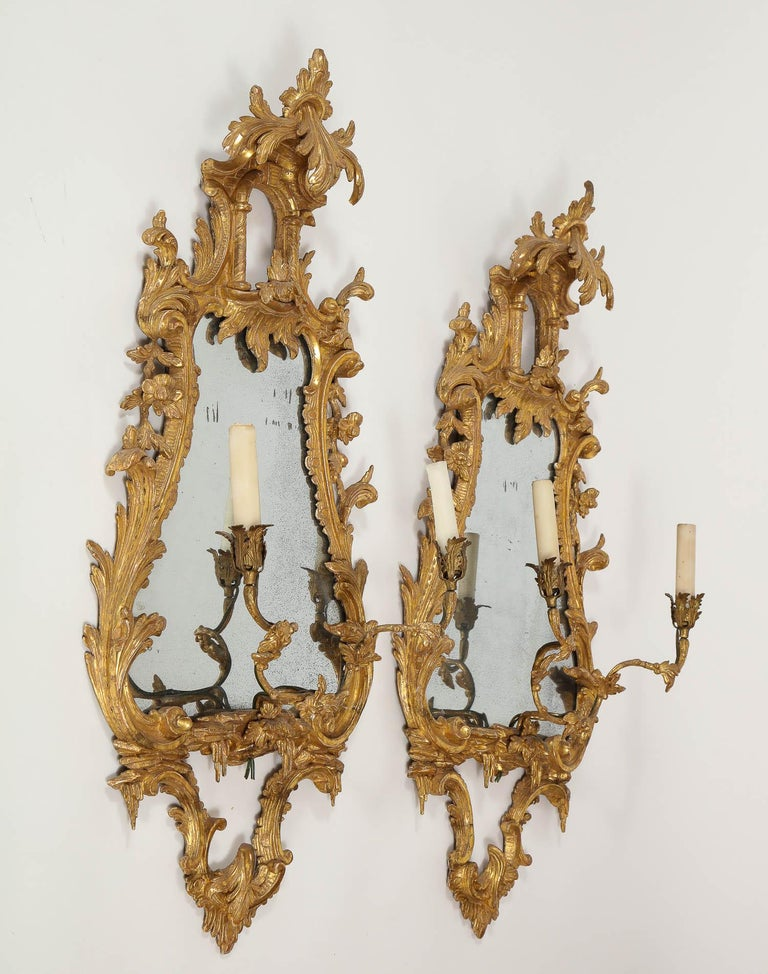 Beautiful pair of antique 18th century George II chinoiserie English carved giltwood mirrors with candleholders. These magnificently hand-carved giltwood mirrors are meticulously detailed and adorned with acanthus leaves flourishing throughout the