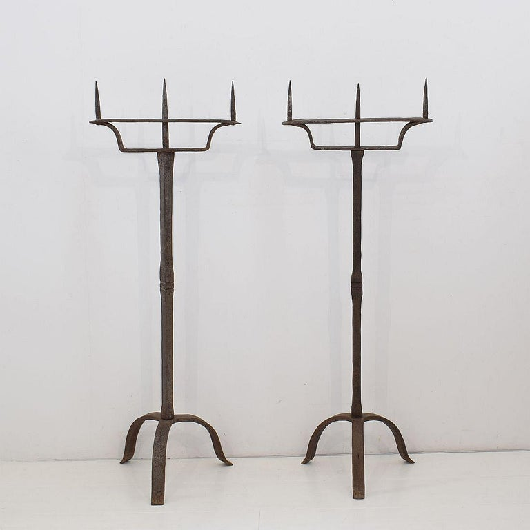 Spectacular pair of hand forged iron candleholders. France, circa 1850. Good condition. Traces of silver paint visible.