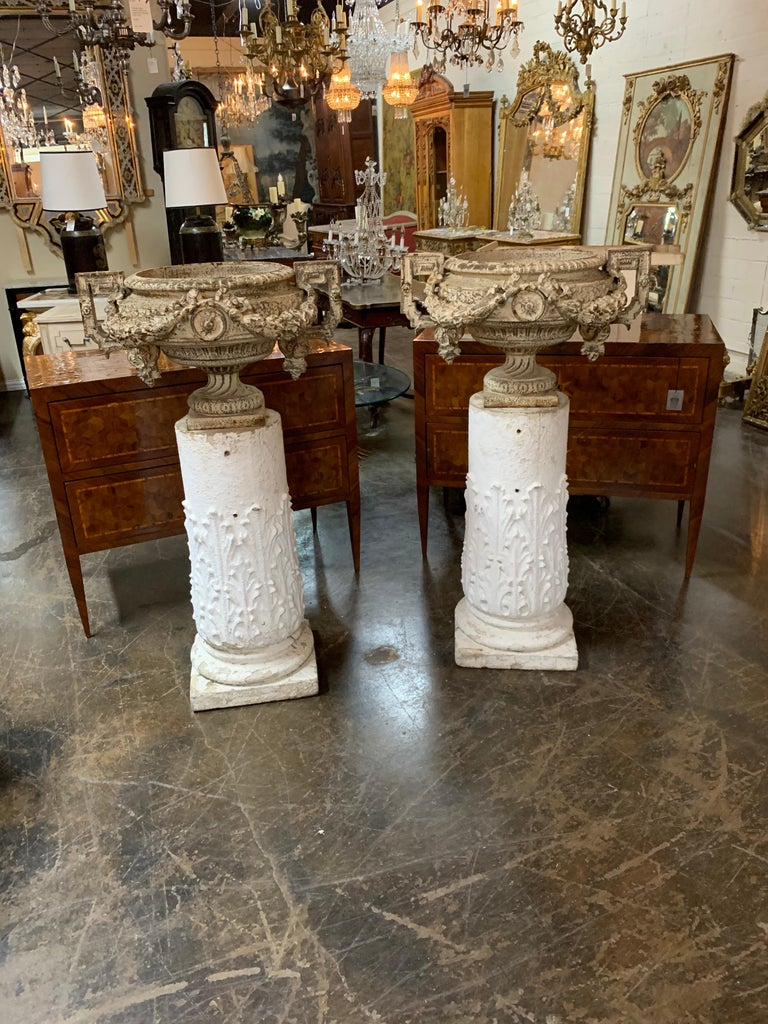 Fine pair of 18th century French iron garden urns on gesso pedestal bases. Ample size on the urns would make for a substantial planting. So pretty!