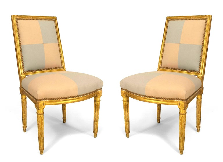 Pair of French Louis XVI (18th Cent) gilt side chairs with square back and upholstered in beige and blue square pattern on seat and back.