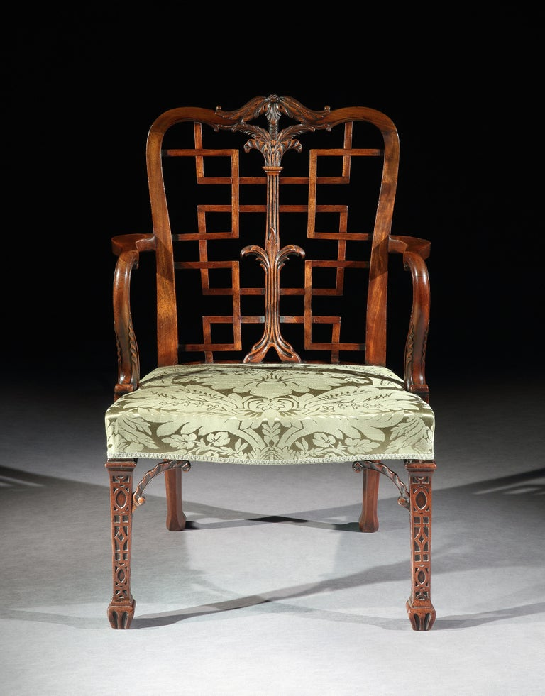 A very fine pair of George III mahogany chinoiserie armchairs in the manner of Thomas Chippendale. The chairs with serpentine top rails carved with acanthus leaves over trellis backs with central palmette splats, above wide serpentine seats and