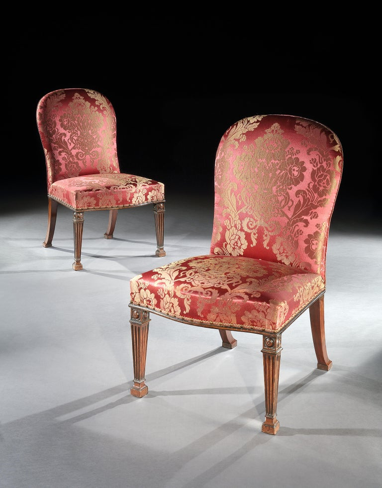 An outstanding pair of George III mahogany side chairs, the upholstered arched back and serpentine fronted seat, raised on finely carved fluted tapering front legs each surmounted by a domed block paterae and terminating in block capital feet, the