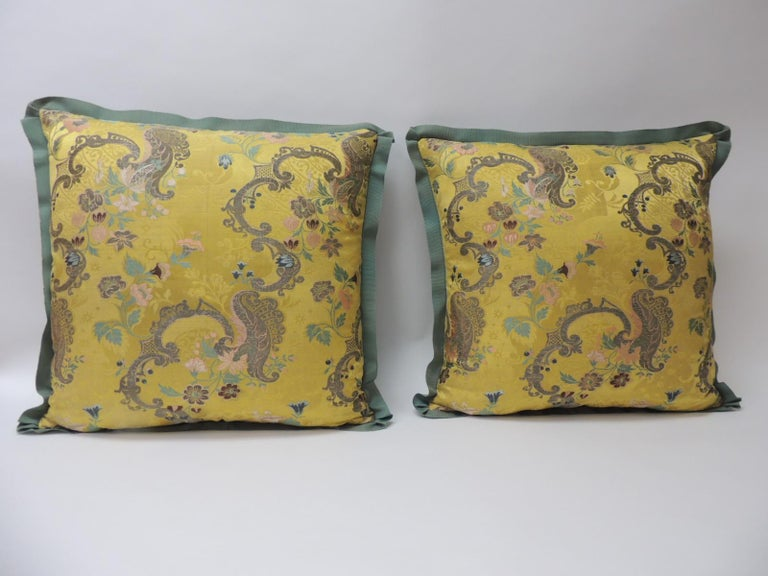 Pair of 18th century green and gold brocaded French silk decorative pillows. Antique textile embroidered with silk and gold metallic threads. Floral pattern depicting flowers in bloom. Strié green silk backings. Embellished with a green French silk