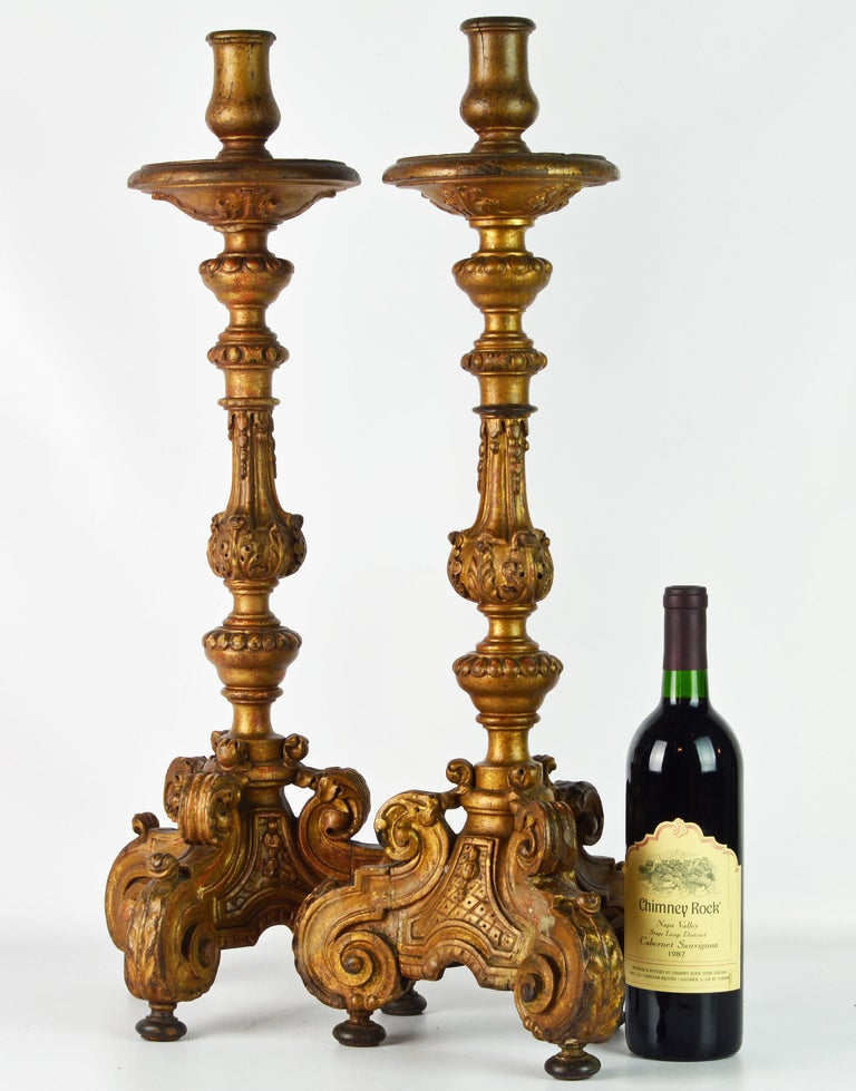 Standing 26.5 inches tall these richly carved Baroque altar prickets are as impressive as they are beautiful. The have the authentic wear and tear to be expected for 18th century artifacts and the original gilt has taken on a pleasant not shiny