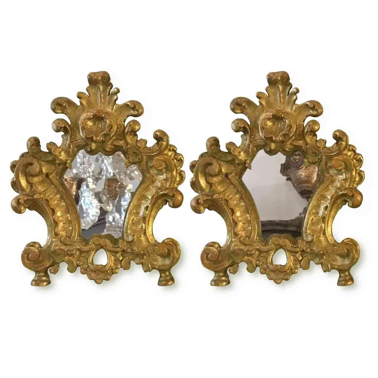 A charming pair of 18th century carved and giltwood mirrors, small altar cards or cantagloria from Italy.  Shaped, with scrolling and vegetal deep carving, they are realized in cembran pinewood and have an original gold leaf gilding, dating back to
