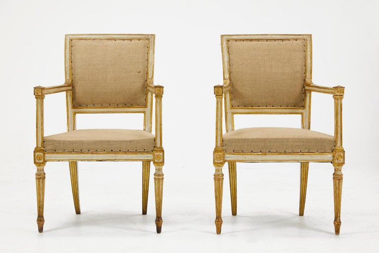 Pair of 18th century Italian armchairs with original cream paint and gilded decoration. Nice model with fabulous patina.  Upholstered in hessian, and fully prepared for recovering.   Measures: Seat height 45.5cm Seat depth 43cm.
