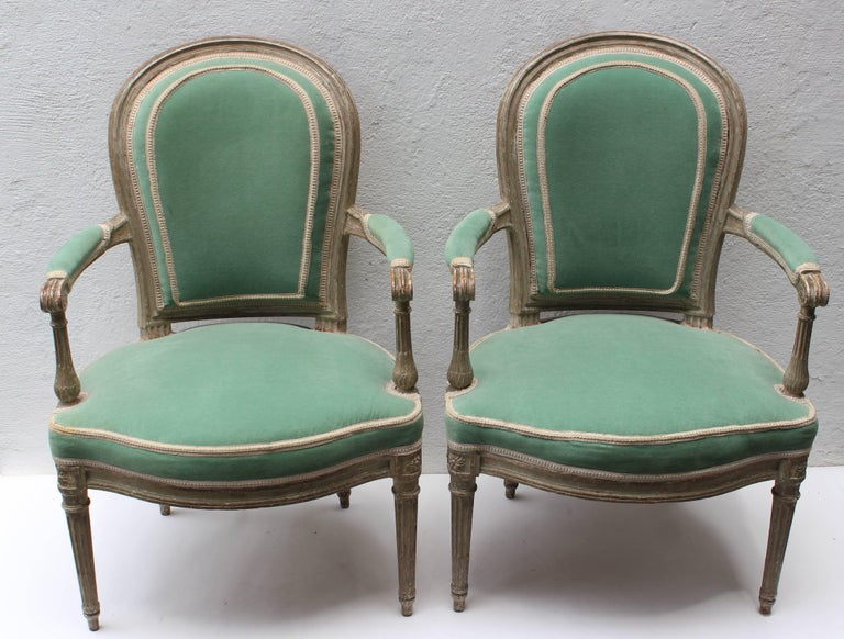 Pair of Louis XVI painted white fauteuils en cabriolet attributed to Georges Jacob (1739-1814) circa 1780.  With round channel-moulded backrest issuing straight scrolled arms with manchettes above serpentine U-form seat, the conforming seatrail