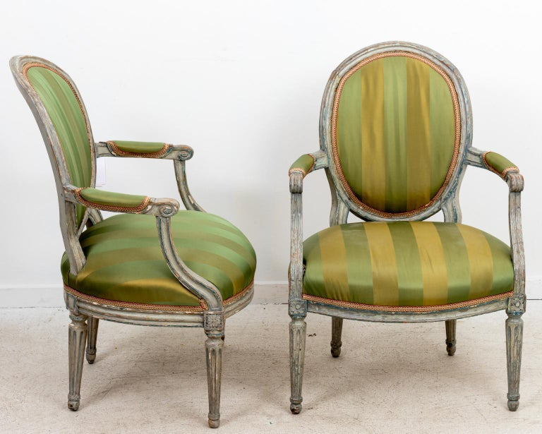 Circa 18th century pair of Louis XV style rounded back armchairs with upholstered seats and turned legs. Please note of wear consistent with age including distressed finish and paint loss to the wood frame.