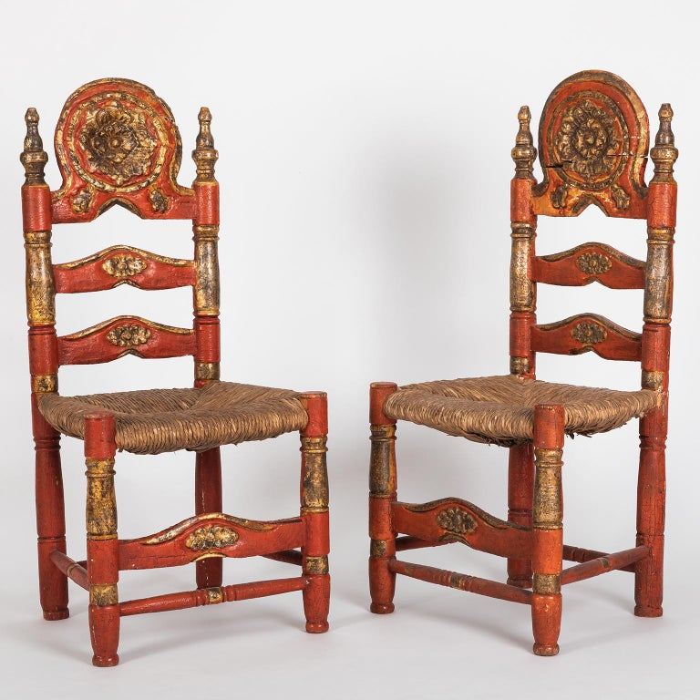 Beautiful and rare pair of Spanish Colonial style ladderback chairs hand painted in red and gold. The wood from the structure is completely hand carved and the seating is handwoven rush. As you can see on the pictures, one of the backs of the