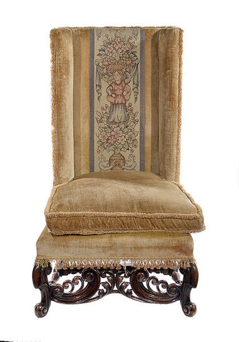 An unusual pair of walnut framed chairs in the style of William and Mary.  The high backs and sides upholstered in a pale beige velvet with an inset multi colored tapestry each depicting a figure surrounded by fruit and flowers to the centre