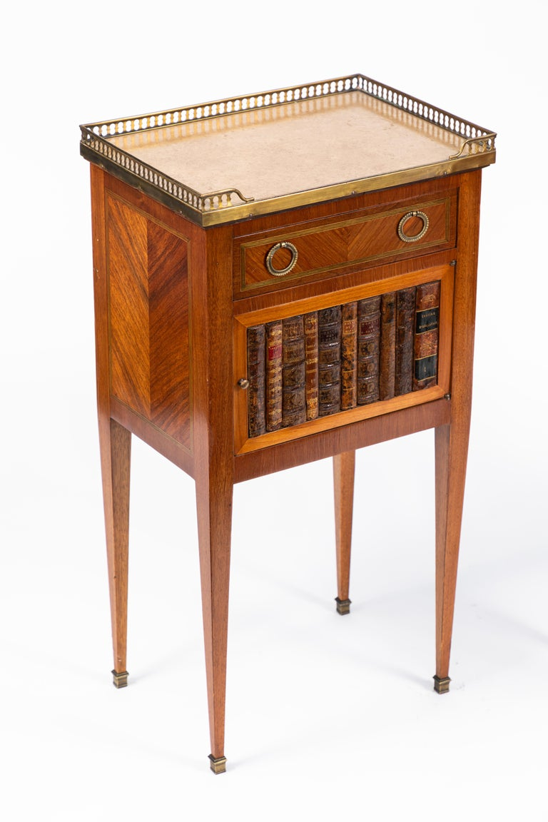 Pair of 1900s French marble-topped end tables with brass pierced gallery. The feet are bronze capped with actual leather bound book binding detail.