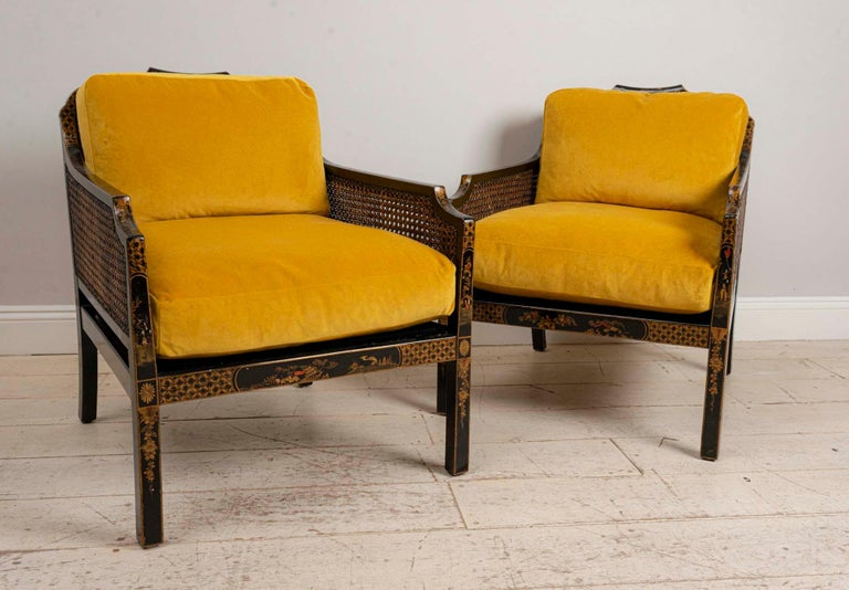 Pair of English 1920s Japanned armchairs with chinoiserie decoration, caned sides and back.