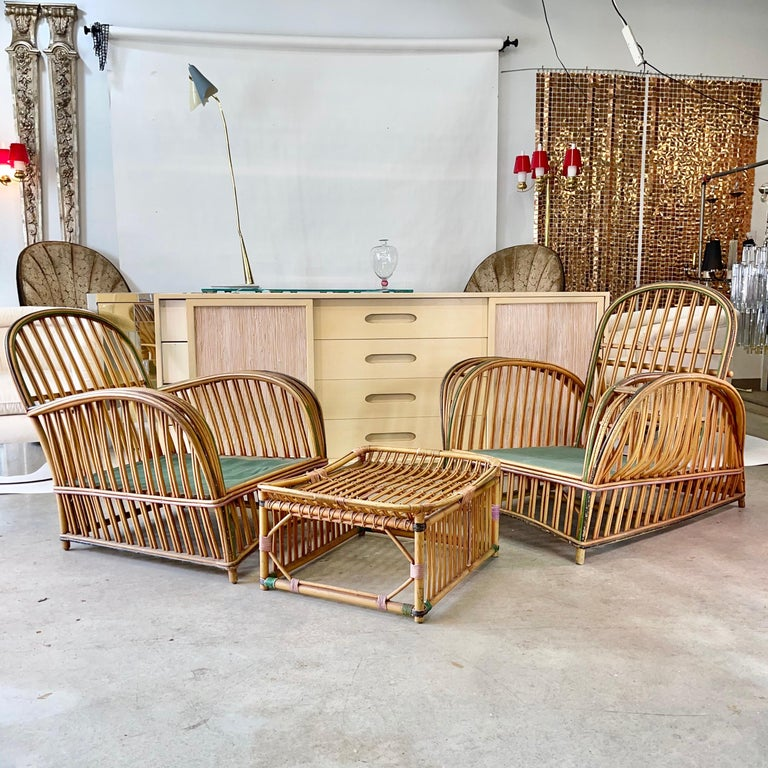Original American Art Deco arch-rounded rattan living room chair ensemble of two chairs and one ottoman by Heywood-Wakefield Co., circa 1925 (both original labels present), with painted trim in forest green, black and pale purple. These came from