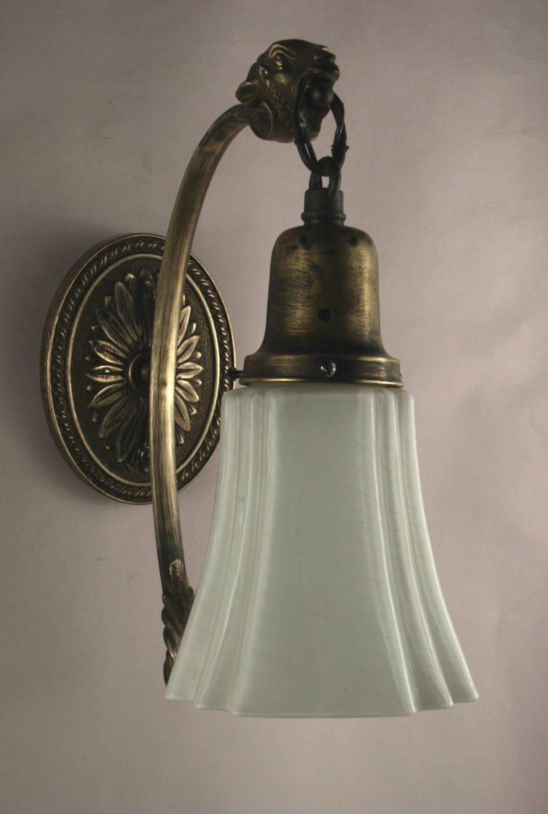 1920s darkened brass single arm sconce ending with a ram head supporting a milk glass shade.