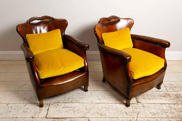 Pair of 1920s Swedish leather club chairs by Otto Schulz, with studded detail and gold velvet cushions.