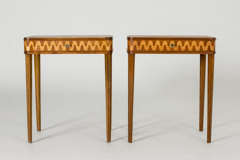 Pair of beautiful bedside tables from NK, with slender tapering legs and drawers with wavy inlays in a lighter wood. This is a married couple, made from different kinds of wood which shows in the different looks of the woodgrain.