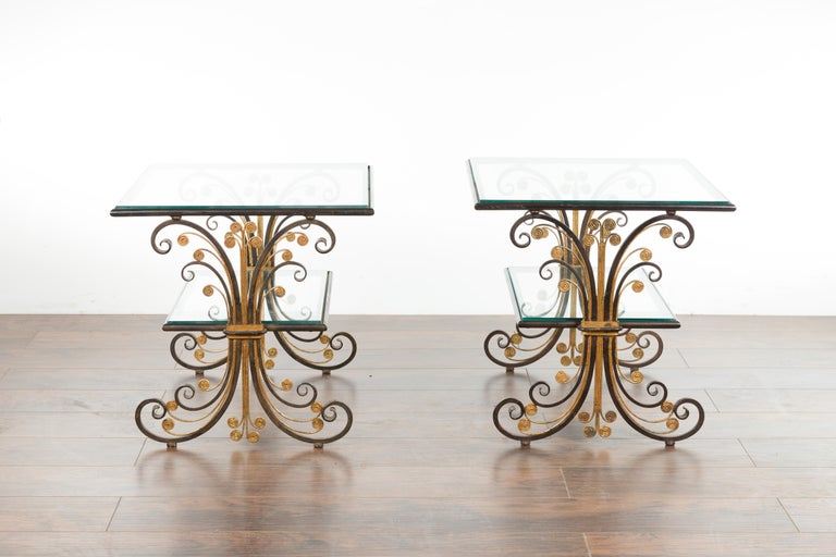 A pair of French Art Deco period iron and brass side tables from the mid-20th century, with scrolling effects and glass tops. Created in France during the second quarter of the 20th century, each of this pair of side tables features a rectangular