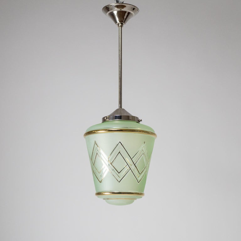 Lovely pair of French Art Deco pendants from the 1940s. Suspended from nickeled brass hardware are lantern-shaped blown glass diffusers with a mint green tint. The glass bodies are frosted on the outside with clear areas and gold paint in a