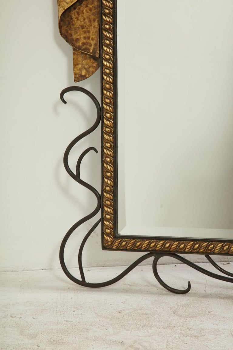Mid-20th Century Pair of Gilbert Poillerat Style Parcel-Gilt and Black Iron Wall Mirrors