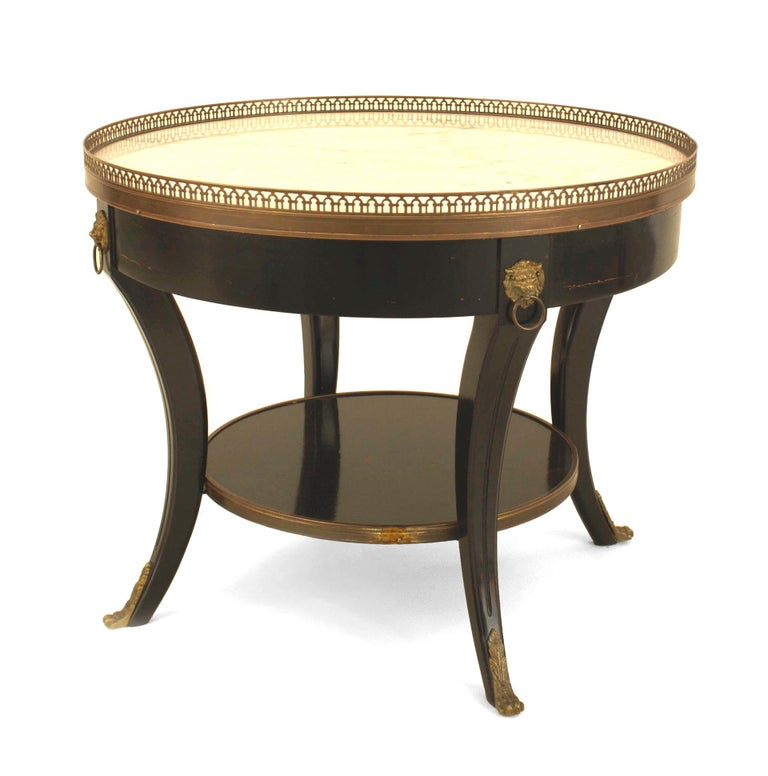 Pair of French 1940s (Louis XVI style) ebonized and bronze trimmed low round end tables with white marble tops having a filigree bronze gallery with a shelf stretcher (Stamped: JANSEN).  Maison Jansen was aParis-basedinterior decorationoffice