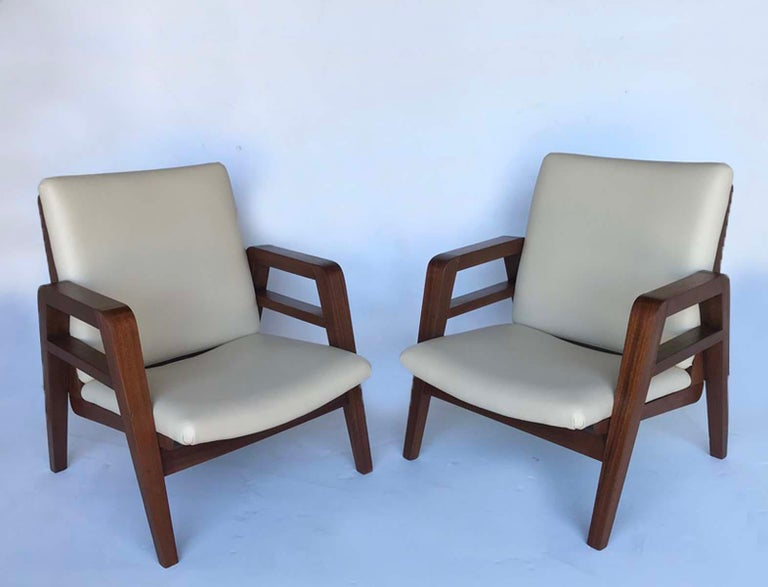 Handsome pair of French 1940s mahogany armchairs. Newly upholstered in cream color embossed leather. Clean lines, great profile. The seat height is 13 inches and the seat depth is 18.5 inches. These are both in very, very good condition with new