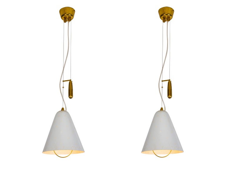Pair of 1940s Paavo Tynell 'A1942' counterweight pendants for Idman Oy. This rare and exceptionally pair is executed in white painted perforated metal and brass, and can be raised and lowered using its ingenious counterweight and pulley system.